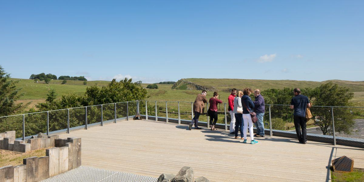 Visitors looking out over Hadrian's Wall from the top of Sill roof.