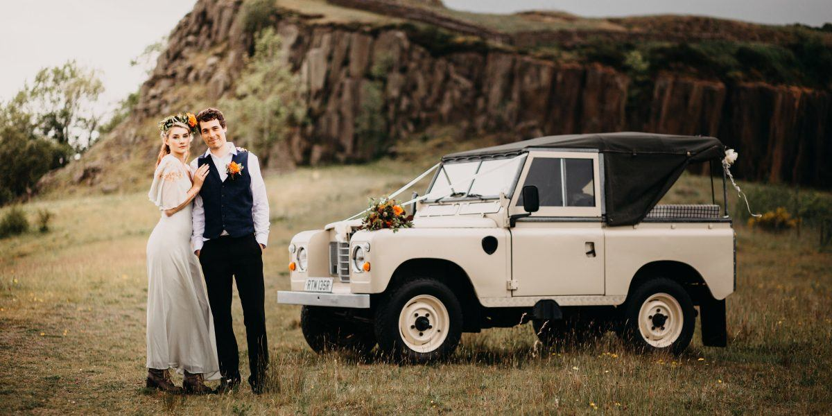 a bride and groom next to a white land rover at walltown