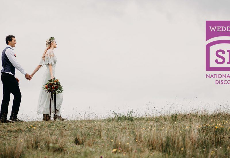 a couple walking hand in hand on grassland with the weddings at the sill logo to their right