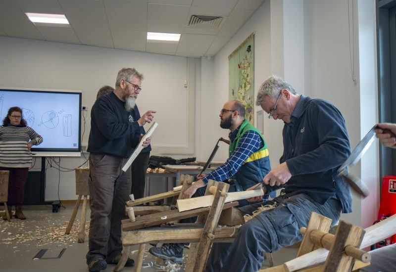 adults sit making wooden stools
