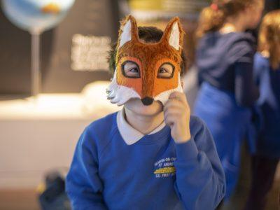 A school child wear a fox mask
