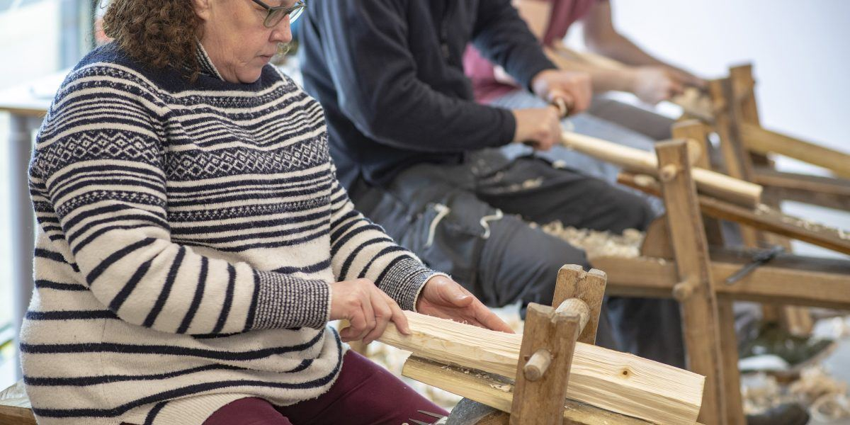 three adults sit making wooden stools