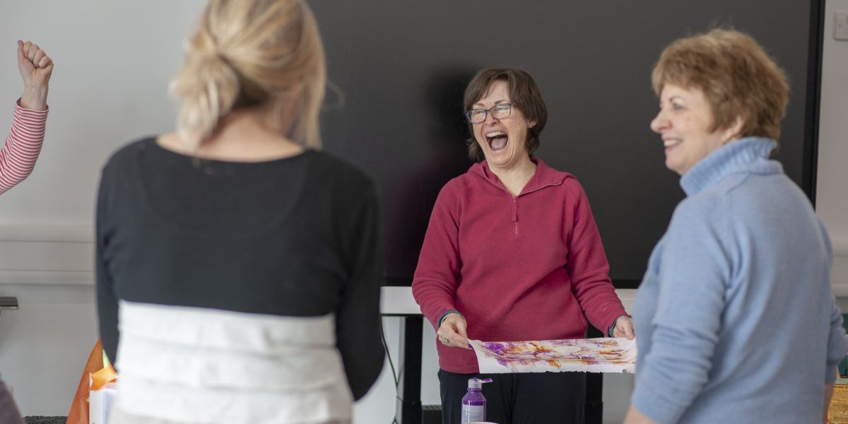 women laugh together as a art session at the sill