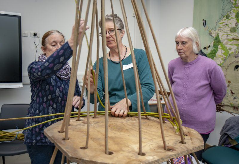 three women weave a basket