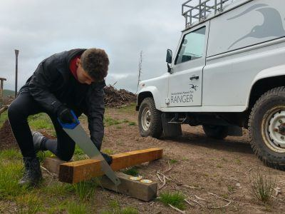 ranger school pupil saws wood next to white land rover