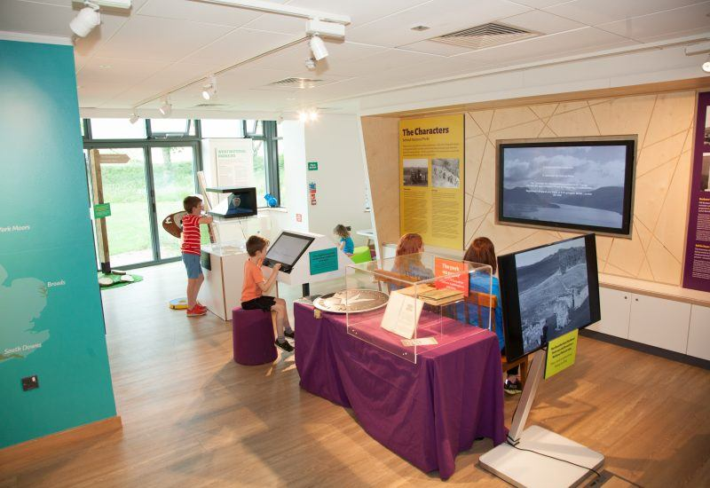 A family visiting the Yours Since 1949 exhibition at The Stell in The Sill