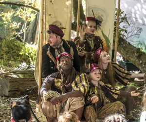 The Cast of Told in Gold performing in a woodland setting