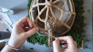 Raffia being added to the roof of the model
