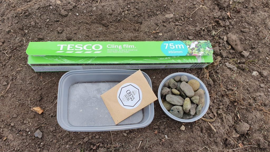 A photo showing two plastic tubs, rocks, seeds and cling film