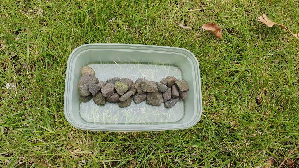 A plastic container with a line of small rocks in the centre.