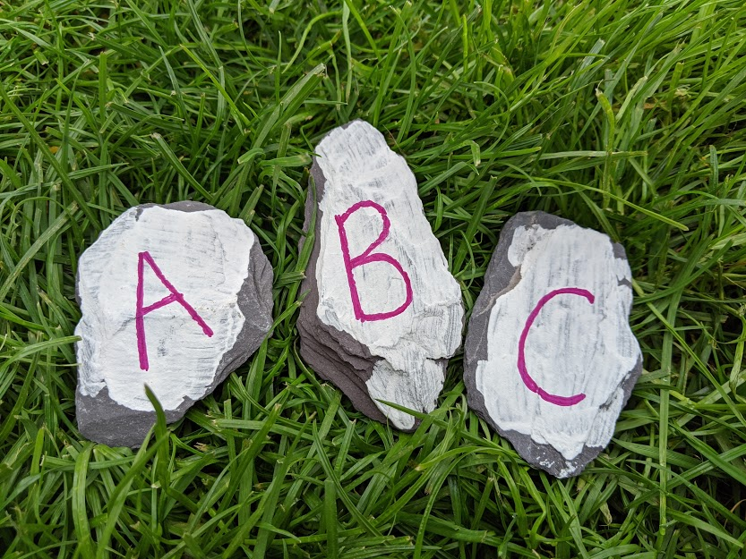 three stones and the letters A, B and C painted on them