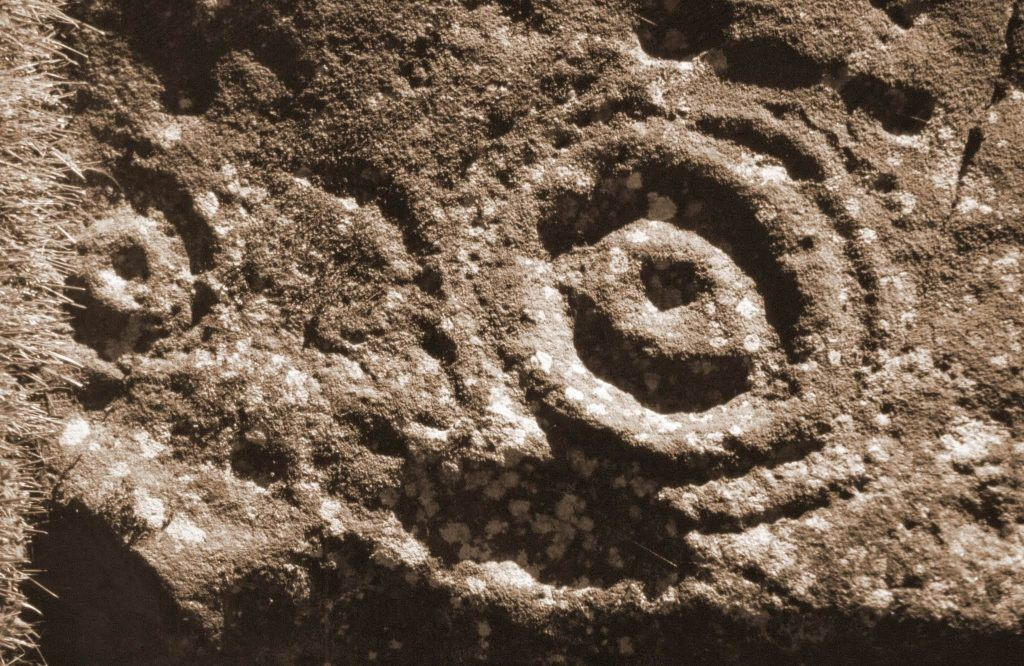 An example of cup and ring rock art etchings; why they were made is a mystery