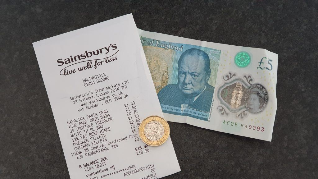 A five pound note, a pound coin and a receipt