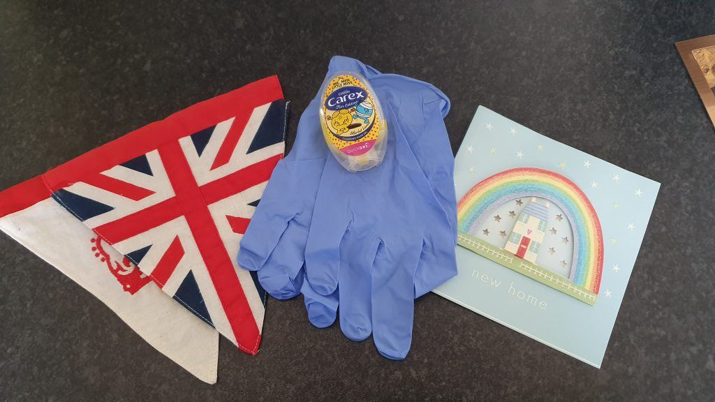 Union Jack bunting, blue gloves, hand santizer and a New Home card