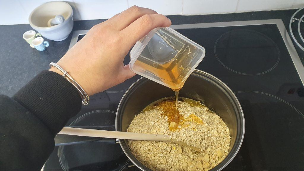 Honey being added to oats and butter in a pan