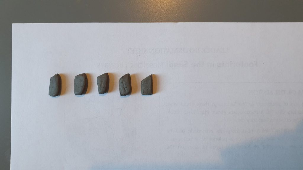 Five small, flat pieces of clay