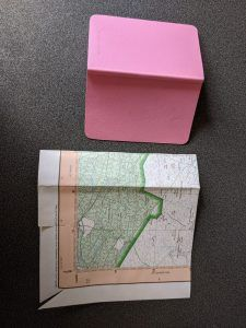 a small notebook next to a paper map