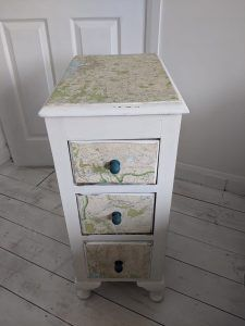 A small set of drawers with maps glued to them