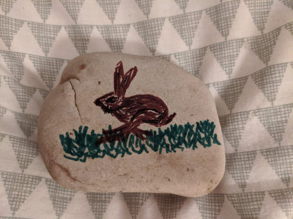 A small rebble with a rabbit painted on it