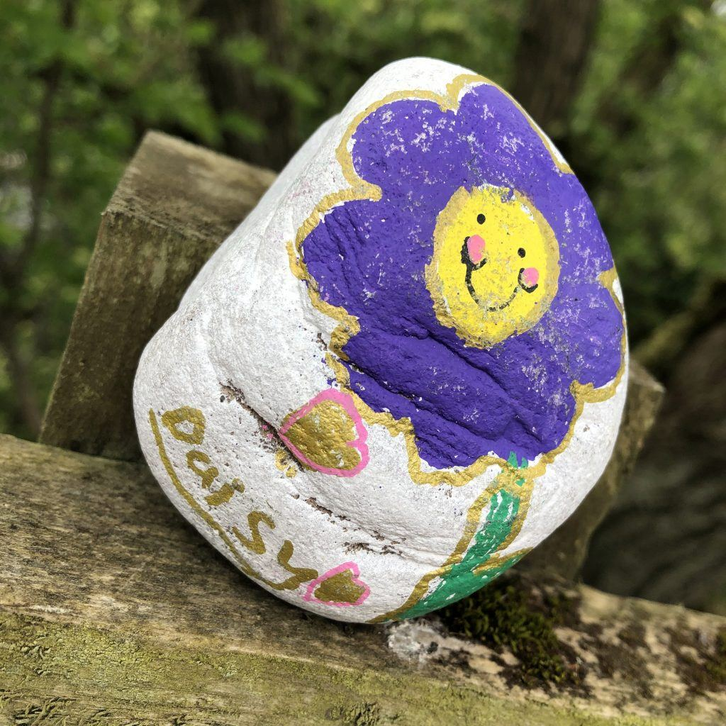 A purple flower painted on a rock