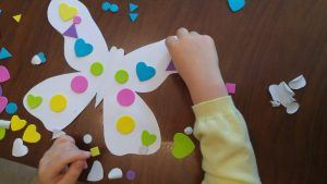 A child decorating a paper butterfly