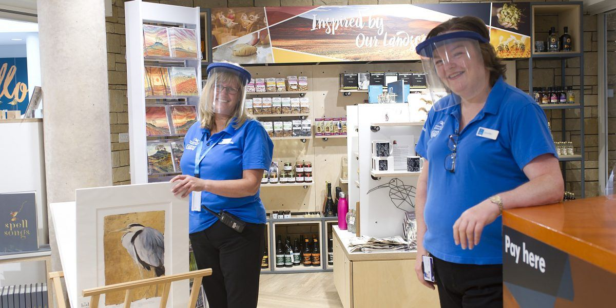 Two members of staff wearing visors in the Sill Shop