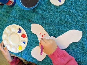 A child painting a paper butterfly