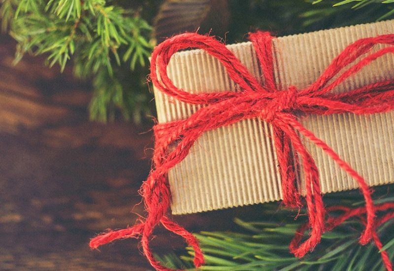 A Christmas present wrapped in brown paper with a red string box around it