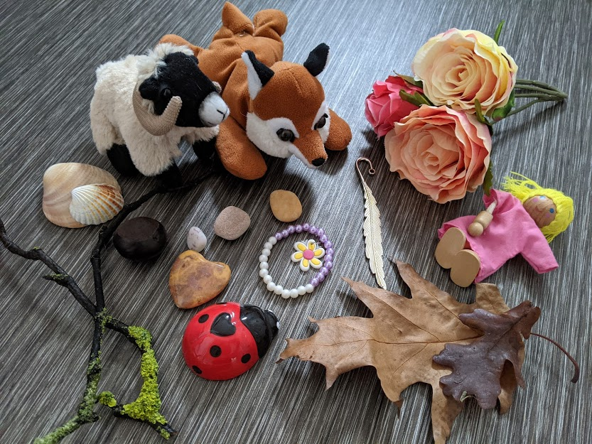A selection of objects including leaves, bracelets and cuddly toys.