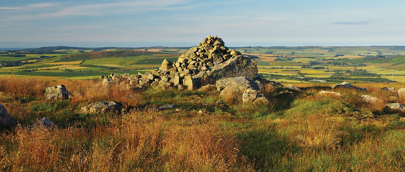 A burial cairn of stones in a field near Wooler, Northumberland