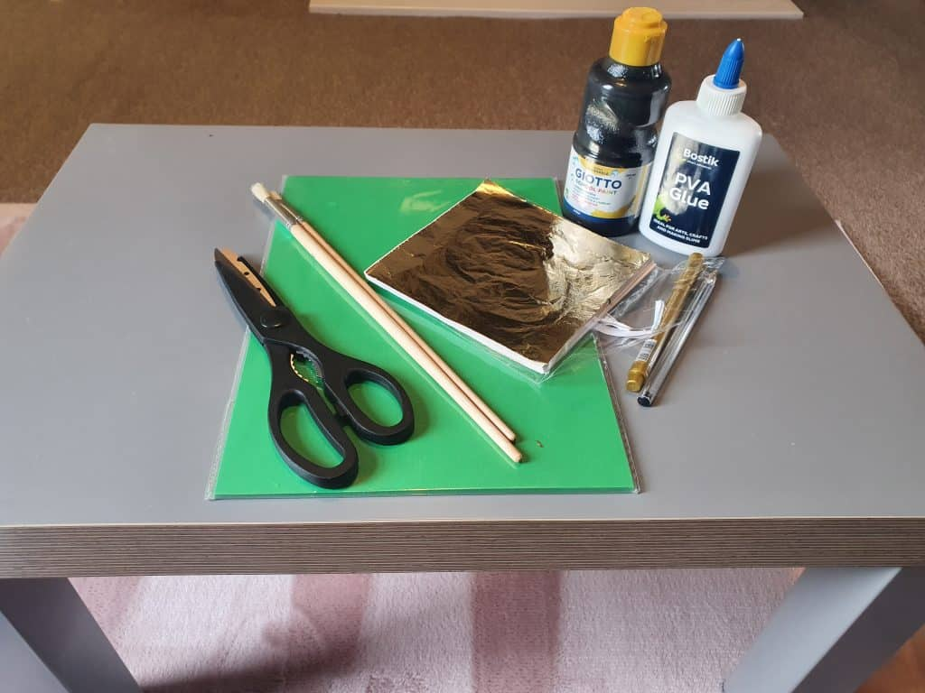 A collection of scraft materials resting on a table. These include scissors, green coloured card and glue.