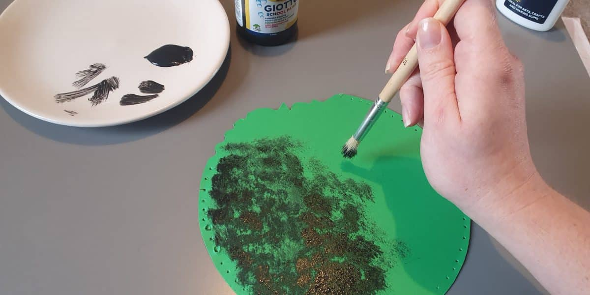 A hand with a paintbrush adds bronze coloured painted to a green card circle