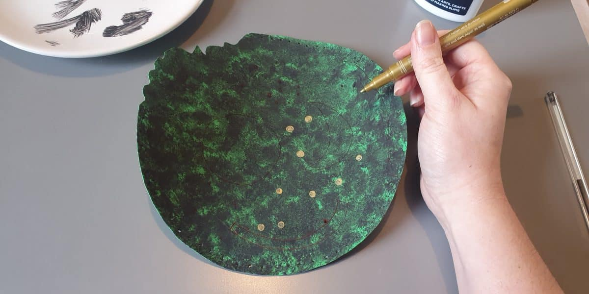 A gpainted circular piece of green card is adorned with stars from a gold coloured pen.