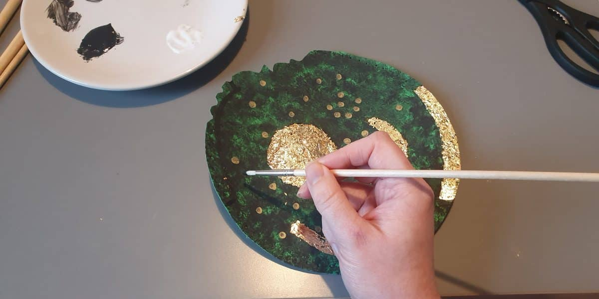 A hand painting some more gold stars on a green piece of card.