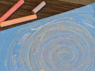 A childs artwork of a swirling galaxy created on card using chalk.