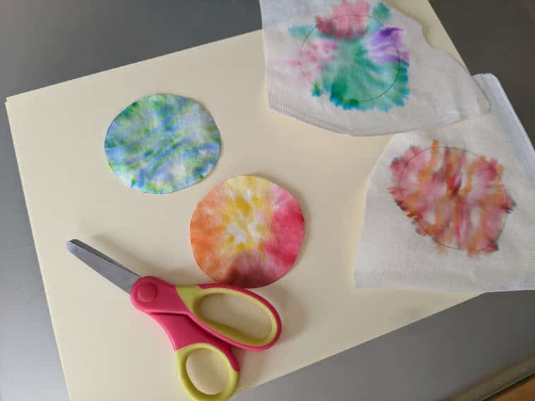 A photo of craft materials showing a pair of scissors and some paper circulars painted in different colours.