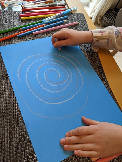 A childs hands drawing swirling circles in chalk on a piece of bllue card
