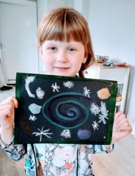 A young girl holding up an illustration of the solar system.