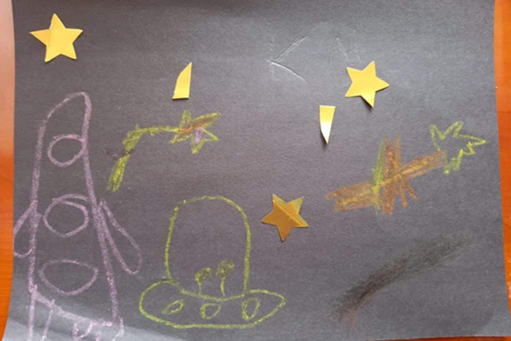 A childs illustartion of a space rocket and stars.