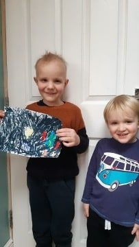 A photographs of two young children with one holding an illustration of the solar system.