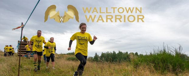 A group of people in yellow t-shirts running with a Walltown Warrior logo above them