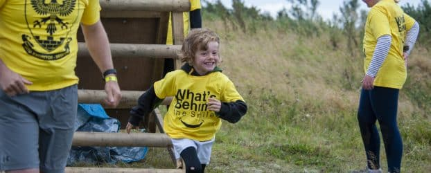 A young boy runs from a wooden ladder at an obstacle race