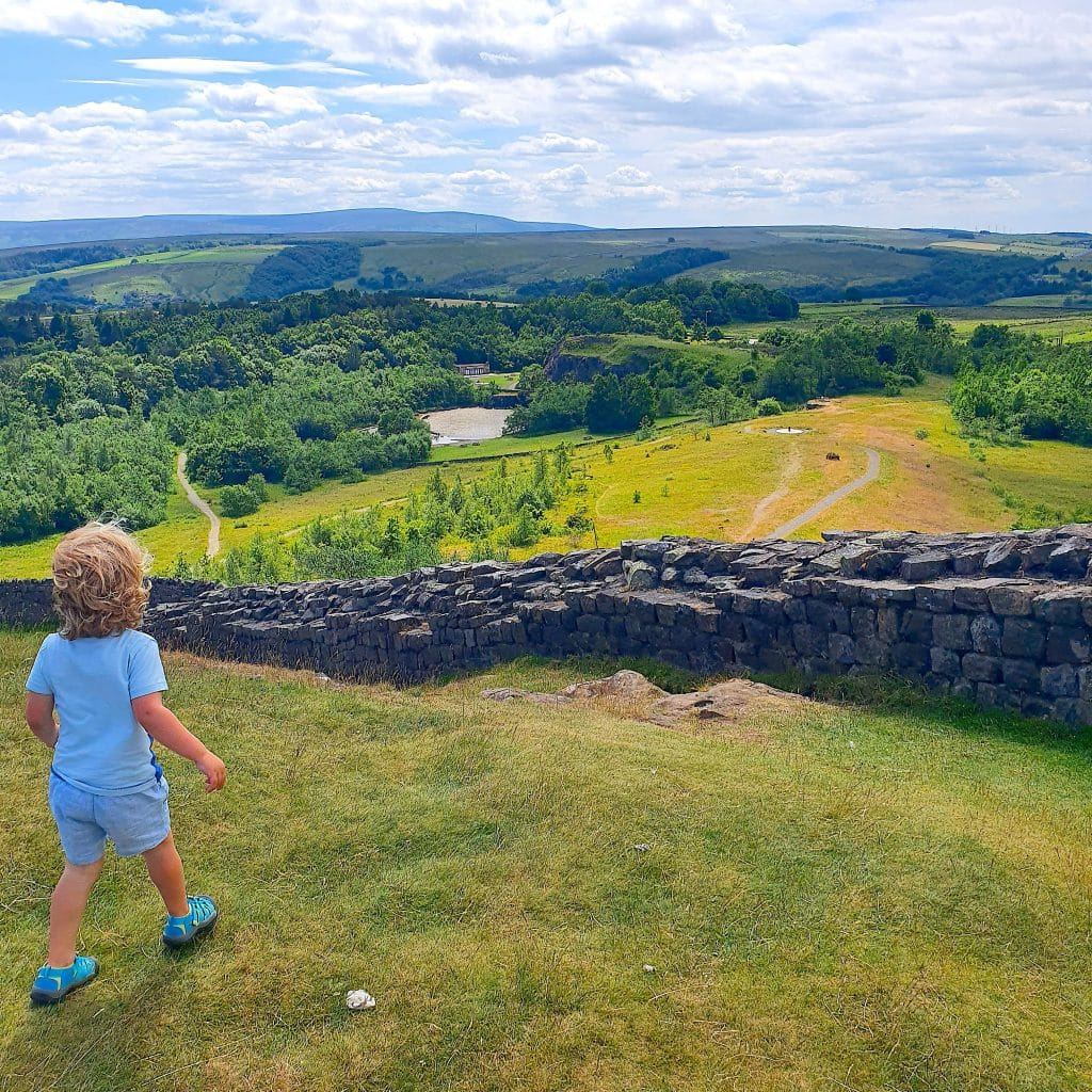 A yong boy with blue shorts, looks out over the expanse of Walltown Country Park from high up on Wallcrags Crags.