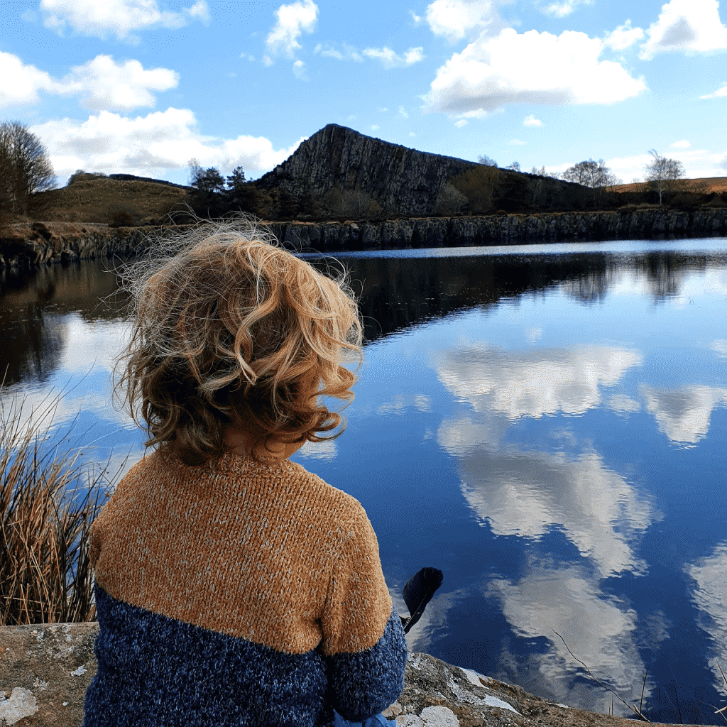 A young boy, with his back to the camera, looks out over the lake at Cawfields Quarry