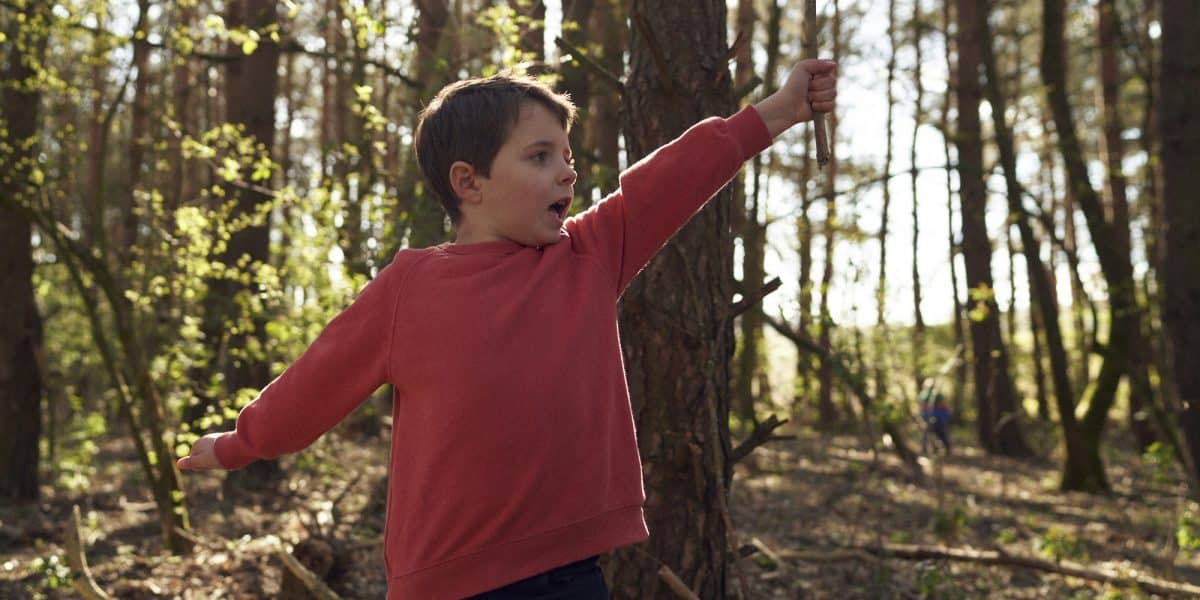 A young boy, wearing a red jumper, plays in a woodland area in Northumberland National Park
