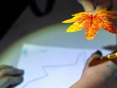 A yellow and red tree leaf is held over a piece of paper while a child's hand traces the outline