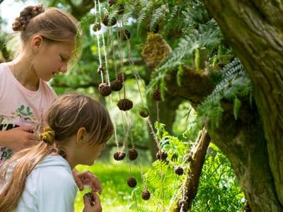 Two young girls hanging conkers from a tree as part of a bushcraft session in the National Park.